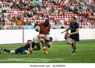 SINGAPORE-APRIL 16:Kenya 7s Team (red) plays against Scotland 7s team (navy blue) during Day 1 of HSBC World Rugby Singapore Sevens on April 16, 2016 at National Stadium in Singapore