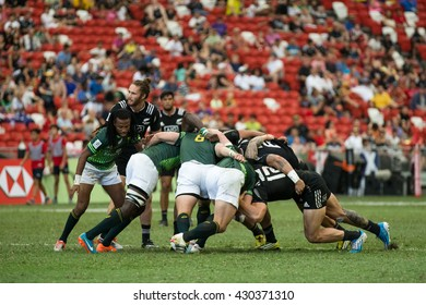 SINGAPORE-APRIL 17:South Africa 7s Team (green) plays against New Zealand 7s team (black) during Day 2 of HSBC World Rugby Singapore Sevens on April 17, 2016 at National Stadium in Singapore