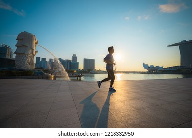 SINGAPORE-APRIL 30, 2018: Healthy man running exercise at Marina Bay Sand park near merlion statue fountain in morning, Singapore. Merlion fountain is the most famous tourist attraction in Singapore.