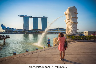 SINGAPORE-APRIL 30, 2018: Merlion statue fountain in Merlion Park and Singapore city skyline at sunrise sky morning. Merlion fountain is one of the most famous tourist attraction in Singapore.