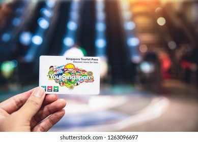 SINGAPORE-APRIL 30, 2018:  Tourist hold Singapore Tourist Pass Card in hand, It use for MRT and LRT trains ftransportation unlimited travel in Singapore city, Singapore