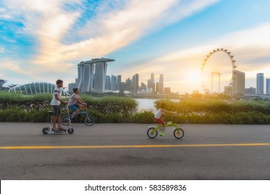 SINGAPORE-JULY 9, 2016: Healthy Asian family exercise with bicycles in the evening sunset time at Marina Bay Sand park, the most famous tourist attraction in Singapore city, Singapore.