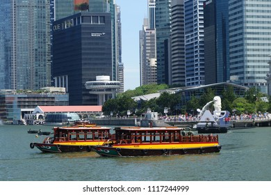 SINGAPORE-JUNE 17, 2018: Classic taxi tourist boat passing in river Marina Bay urban skyscrapers with Merlion statue fountain in Singapore.
