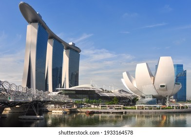 Singapore-May 2020: Low angle view of the ArtScience Museum and Marina Bay Sands hotel with their respective iconic shapes against a blue sky