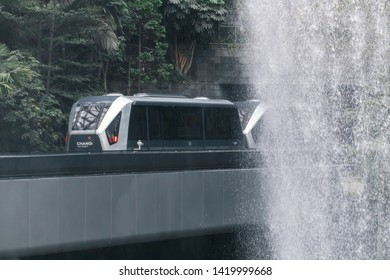 SINGAPORE-MAY 22, 2019_Skytrain in The HSBC Rain Vortex, the world's largest indoor waterfall in Jewel Changi Airport. The skytrain connects Changi terminals 1, 2 and 3, cuts through middle of Jewel