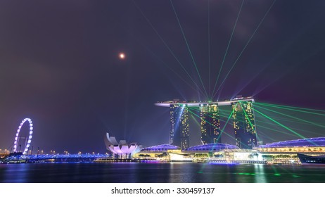 SINGAPORE-SEP 27, 2015: Full moon and lighting, laser show over Singapore landmarks and tourist attractions Marina Bay Sands, Singapore Flyer, ArtScience Museum, The Shoppes. View from Merlion Park
