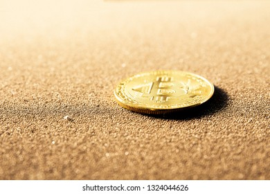Singel bitcoin laying down on a dark brown background. Oldest cryptocurrency stands for digital gold.