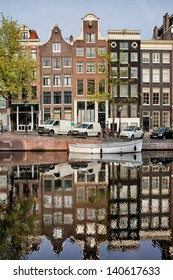 Singel canal historic terraced houses with reflection on water in the city of Amsterdam, Netherlands.