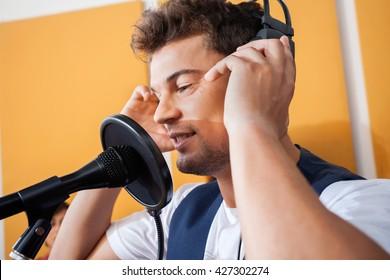 Singer Adjusting Headphones While Singing In Recording Studio