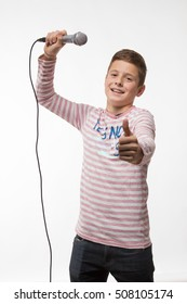 singer brunette boy in a pink jumper with a microphone on a white background
