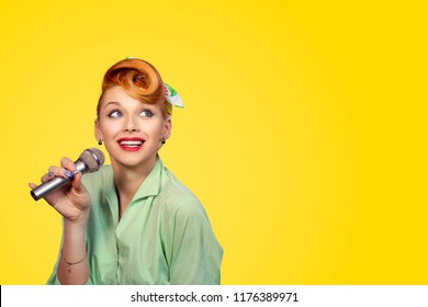 Singer. Closeup portrait head shot sexy beautiful happy young woman lady pinup 50s girl singing with microphone smiling daydreaming looking at yellow background wall copyspace Positive face expression