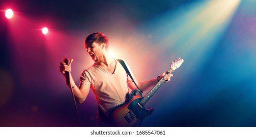 Singer with a guitar and microphone on the stage in stage lighting