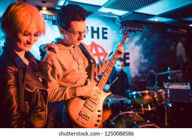 Singer and guitar player on stage during band gig or concert