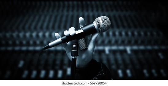 singer hands holding microphone on studio mixer background. hands sign mean love,  concept = love to sing