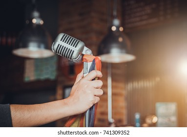 Singer hands holding microphone on stage,Pub,Bar,Restaurant.