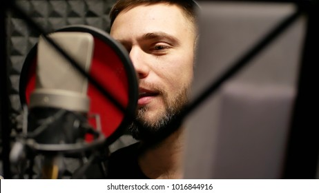 Singer man emotionally writing a song in the recording studio. Records a new melody or song