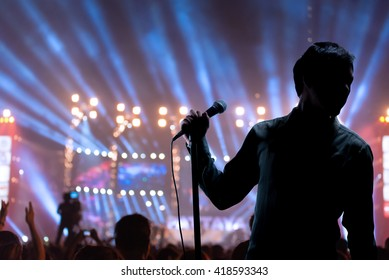 Singer Man posing and singing on concert stage with ray of illuminated