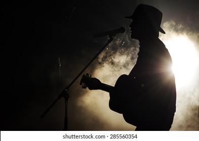 A singer man silhouette playing guitar