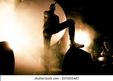A Singer is on the stage. A silhouette of the singer is putting his foot on a speaker. A brutal shadow of a rapper on the stage. Smoke and bright soft yellow stage lights in the background.