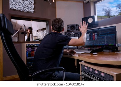 Singer recording a musical theme, in a recording studio