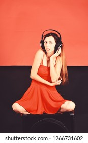 Singer with sly face listens music. Dj sits on black boombox on red and black background. Girl with loose hair wears headphones and red dress. Relax, party and music concept.