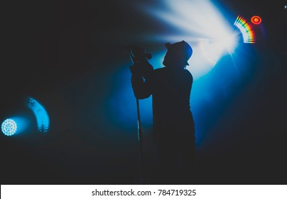 singer / vocalist in a hat performing on stage at a concert in the fog. Dark background, smoke, concert  spotlights.