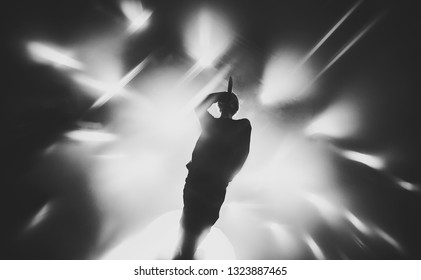 singer / vocalist performing on stage at a concert in the fog. Dark background, smoke, concert  spotlights.