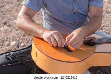 A singer's hands tuning his guitar.