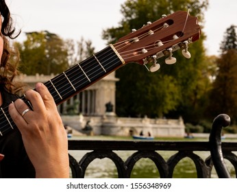 singer-songwriter with guitar in the lake-side retreat park