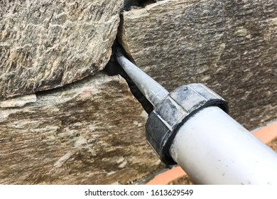 Singing the gaps between the wild stone on the cladding of the foundation. Facing the foundation of a house