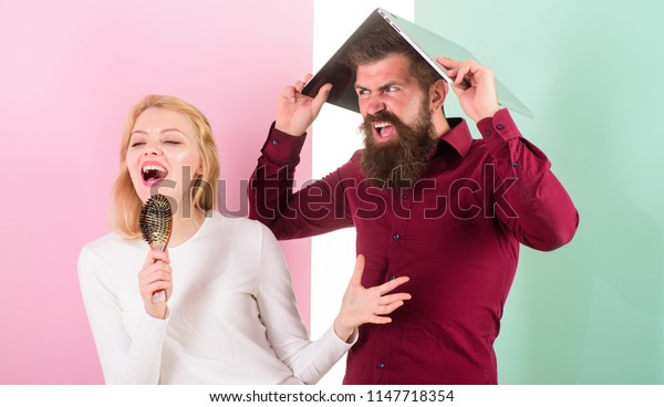 Singing is her passion. Lady sing using hair brush as microphone while man annoyed hiding under laptop. Better sing at talent show than at work. Lady imagine she is superstar talented singer.