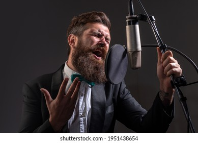 Singing man in a recording studio. Expressive bearded man with microphone. Karaoke signer, musical vocalist