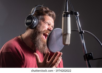 Singing man in a recording studio. Expressive bearded man with microphone. Sound producer. Karaoke signer, musical vocalist.