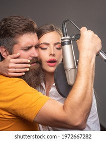 Singing man and woman in a recording studio. Sensual couple with microphone. Karaoke signer, musical vocalist.