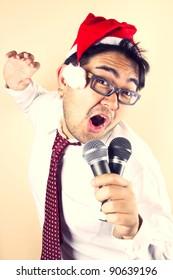 Singing Santa, businessman wear Santa hat singing with two microphone.