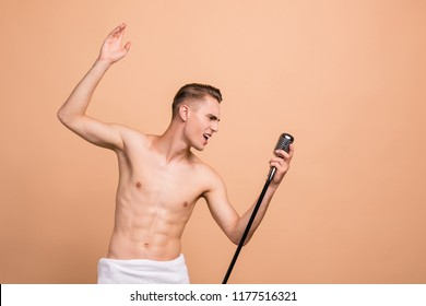 Singing in the shower, rest, relax concept. Profile side view photo of handsome attractive man, singing hit with open mouth in microphone gesture with hand isolated on pastel beige background