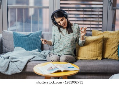 Singing song with emotion.Practicing vocal abilities. Improving range.Cheerful woman listening to music with large headphones and singing.Relaxing with music,happy woman singing.Positive mood