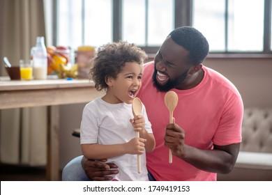 Gesang. Cute Kind mit lockigen Haaren und Vater mit Löffeln und Gesang
