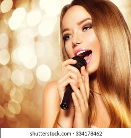 Singing Teenage Girl with microphone over golden glowing background. Karaoke party. Beauty teen model girl singer with a microphone singing and dancing. Disco party. Holiday Celebration
