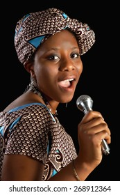 Singing young Ghanese african woman against a black background