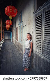 Singkawang, Indonesia 17.08.2020: tourist standing by the wall of a traditional wooden old chinese house decorated with red lanterns