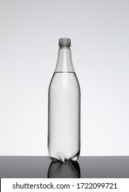 Single 1 litre clear plastic bottle with no label containing a clear liquid against a plain background