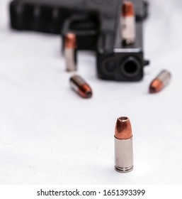 A single 9mm hollow point bullet in front of a black 9mm pistol, blurred behind it with four bullets next to the gun on a white background