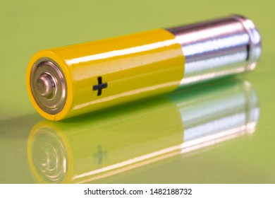 Single AAA battery is seen on a reflective green surface. Closeup view from the plus side of the battery.