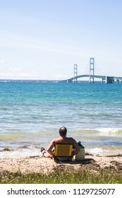 A single adult man, middle aged with dark hair and a bald spot, sits on the southern shore of Michigan's upper peninsula in St. Ignace, back to camera, overlooking Lake Huron and the Mackinac Bridge.