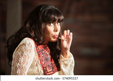 Single adult woman with uneasy expression smoking a marijuana joint
