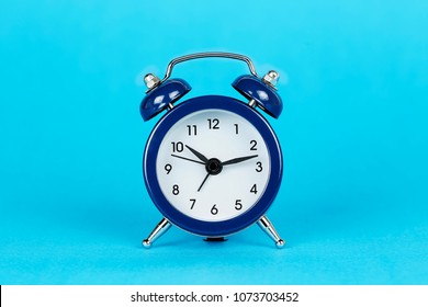 single alarm clock on blue background with copy space