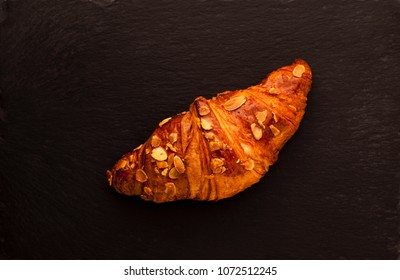 Single almond croissant on black slate base
