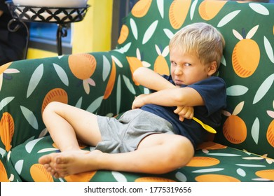 Single angry boy frowned nose, sitting on a multi colour sofa in the living room in a house indoor, crossing hands. Family relationship, childhood problems and behaviour