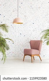 Single armchair, chandelier and leaves of plants set on a dotted wall in hotel lobby interior. Real photo